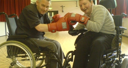 Two people who use wheelchairs with boxing gloves